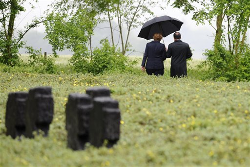 French President Francois Hollande, left, holds an umbrella as he walks beside German Chancellor Angela Merkel at a German cemetery in Consenvoye, northeastern France, Sunday May 29, 2016, during a remembrance ceremony to mark the centenary of the battle of Verdun. Hollande and Merkel are marking 100 years since the 10-month Battle of Verdun, which killed 163,000 French and 143,000 German soldiers and wounded hundreds of thousands. (Jean Christophe Verhaegen/Pool Photo via AP)